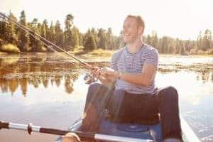 Young Man Fishing From Kayak On Lake