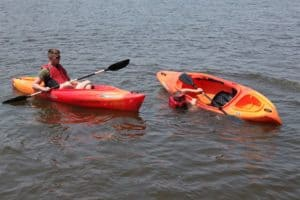 Capsized kayak and partner